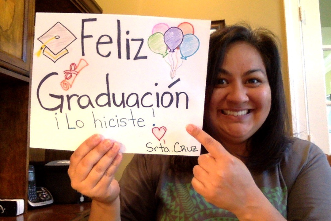 srta cruz holding a happy graduation sign in spanish
